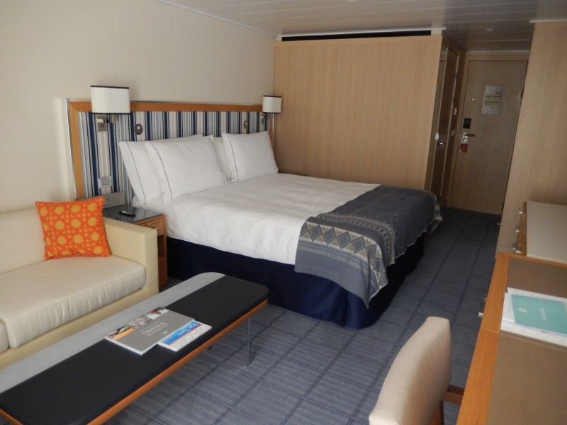 """Our stateroom. The veranda with two chairs and a table is """"behind"""" the foreground of the picture; sofa and easy chair on the left; dresser and desk on the right; bathroom behind the wooden wall beside the bed; double closet across from the bathroom. It's like a large hotel room with an outdoor porch."""