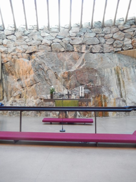 The rock wall behind the altar goes all the way around the circular church. The white upper part of the photo is the skylight ceiling. Of course, it's a Lutheran church.