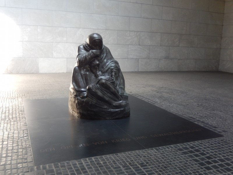 The open roof of the memorial building exposes the sculpture to the elements, symbolic of the woman's suffering.