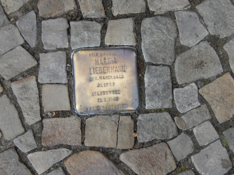 """Berlin doesn't want to forget. This is a """"single stone,"""" set very slightly higher than the surrounding cobblestones. Each one is inscribed with a name and placed in front the house from which that person """"disappeared."""""""