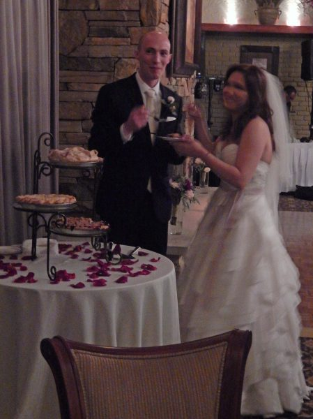 The bride and groom sharing a piece of wedding pie