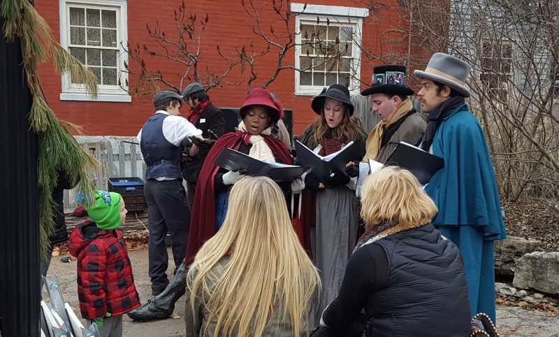 The carolers singing beside the sidewalk.