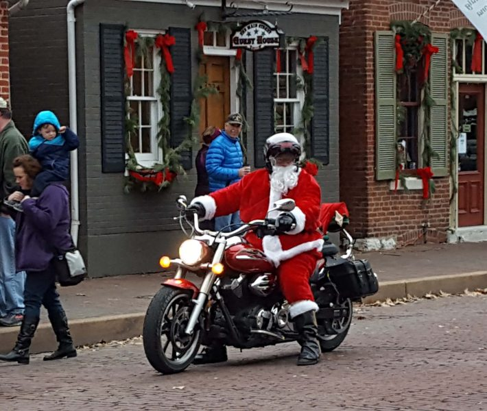 "This might be a modern Santa. I don't think it's a ""period"" motorcycle. Notice the trimmings on the shops in the background. The whole street is decorated like this."