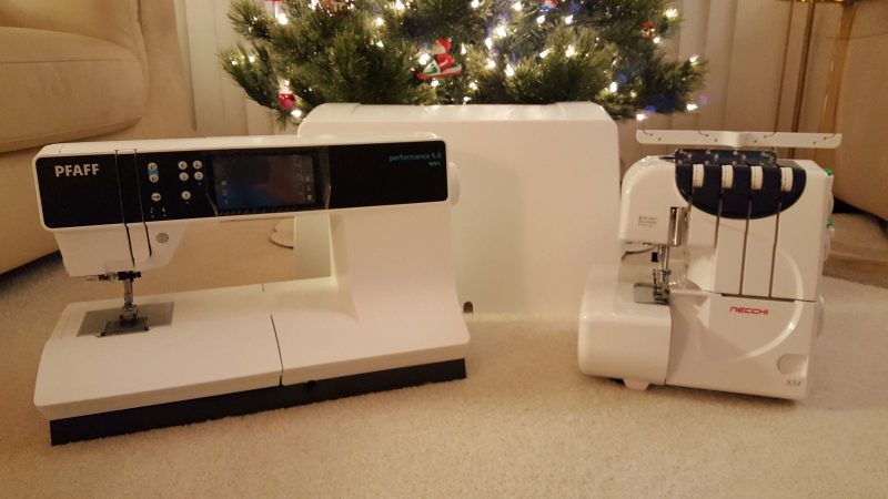 Sewing machine on the left; its case in the back; serger on the right.